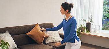Γυναίκα που φοράει SRS-NB10 ασύρματο ηχείο με στήριγμα λαιμού σε λευκό χρώμα και τακτοποιεί έναν καναπέ