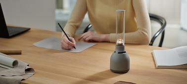 Το ηχείο για κρυστάλλινο ήχο Sony LSPX-S3 τοποθετημένο σε γραφείο, δίπλα σε άτομο που εργάζεται.