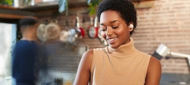 Γυναίκα σε κουζίνα που φοράει τα ακουστικά WF-1000XM4