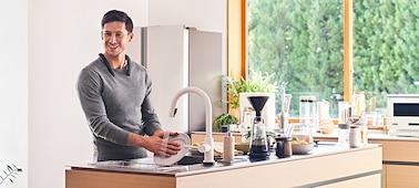 Άντρας πλένει πιάτα στον νεροχύτη φορώντας το ασύρματο ηχείο με στήριγμα λαιμού SRS-NB10 σε μαύρο