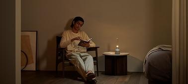 Το ηχείο για κρυστάλλινο ήχο Sony LSPX-S3 σε τραπέζι, δίπλα σε άτομο που διαβάζει, με το απαλό φως αναμμένο.