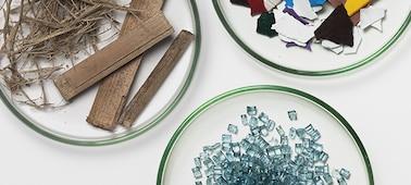 Λήψη από ψηλά τριών πιάτων που περιέχουν διαφορετικά υλικά: ξύλο, φυτικές ίνες, κομμάτια καθαρού γυαλιού και πολύχρωμα θραύσματα πλαστικού