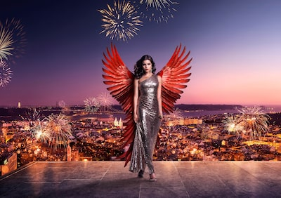 kenton-thatcher-sony-alpha-9-model-with-angel-wings-stands-atop-a-building-with-lisbon-cityscape-behind
