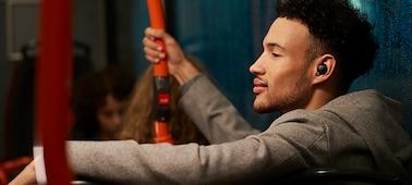 Άντρας σε λεωφορείο το βράδυ με ακουστικά WF-1000XM4