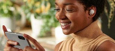 Γυναίκα που φοράει ακουστικά WF-1000XM4 και παρακολουθεί περιεχόμενο smartphone