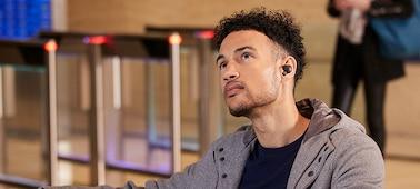 Άντρας που περιμένει σε παγκάκι σταθμού, φορώντας ακουστικά WF-1000XM4